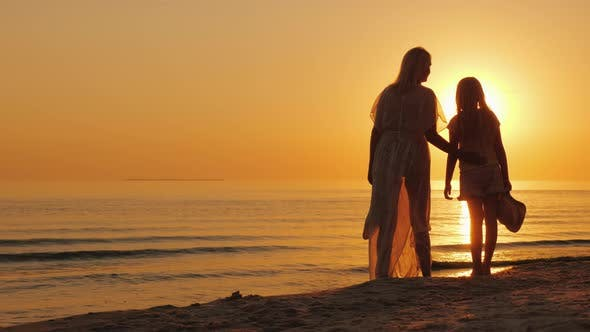 Cover Image for Mom and Daughter Are Looking Forward To a Beautiful Sunset Over the Sea. Silhouettes of a Woman with