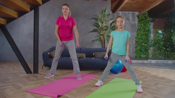 Fit Mutter und Tochter machen Dumbbell Lateral Squat
