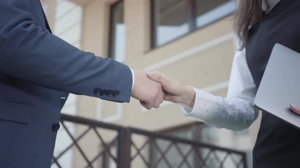 Thumbnail for Two Young Unrecognized Man and Woman Business Partners Shaking Hands on the Terrace Close-up
