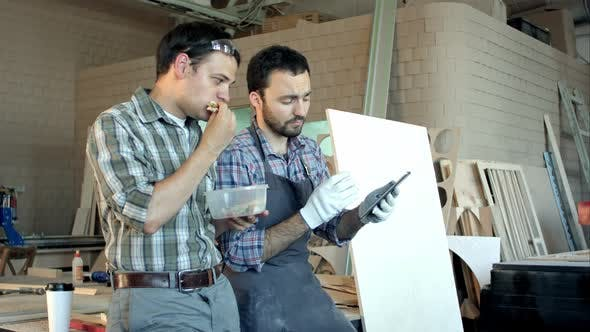 Thumbnail for Two Carpenters Discussing Work and One of Them Eating in Workshop