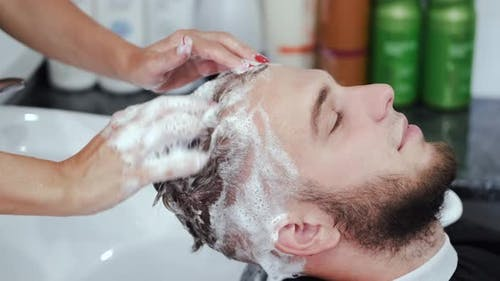 Hairdresser Washing Client's Head with Shampoo in Beauty Salon