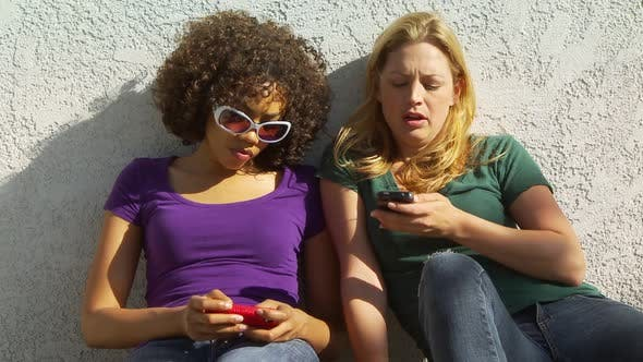 Thumbnail for Two women friends playing with cellphones