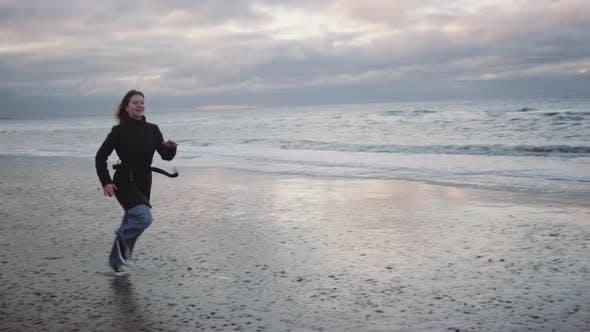 Thumbnail for Redhead In Black Running Along Beach