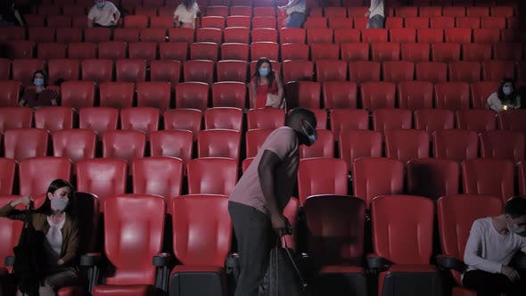 Diverse Audience in Masks Taking Seats in Cinema