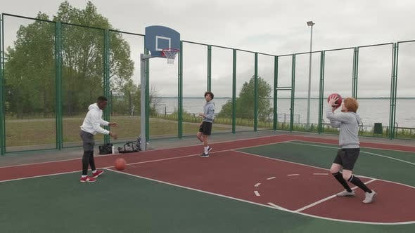 Group of Friends Shooting Hoops Outside