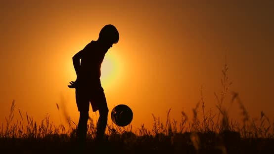 Thumbnail for Silhouette of a Boy Playing Football at Sunset. A Boy Juggles a Ball in the Field at Sunset