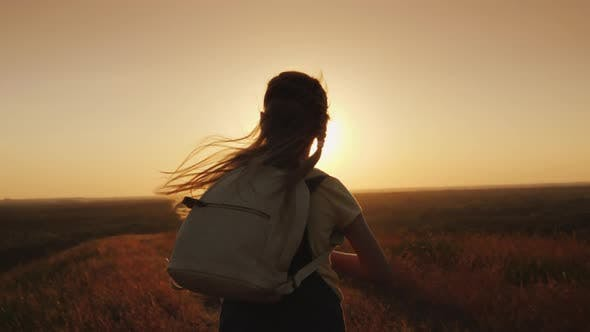 Thumbnail for A Long-haired Child with a Backpack Runs Towards the Sun