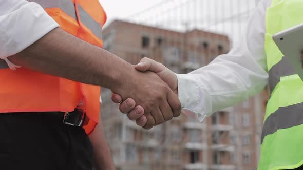 Thumbnail for Two Architects Engineers Shaking Hands at Construction Site. Close Up.