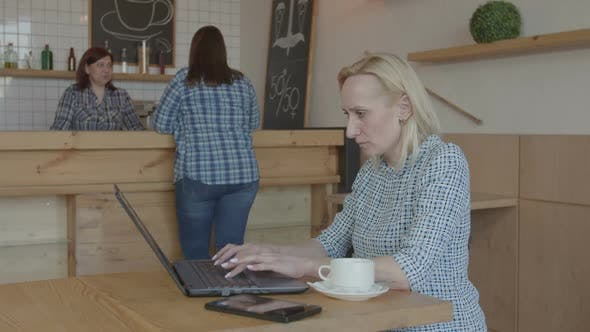 Pensive Female Blogger Working on Laptop in Cafe