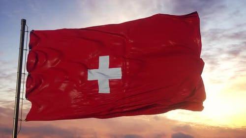 Flag of Switzerland Waving in the Wind Against Deep Beautiful Sky at Sunset