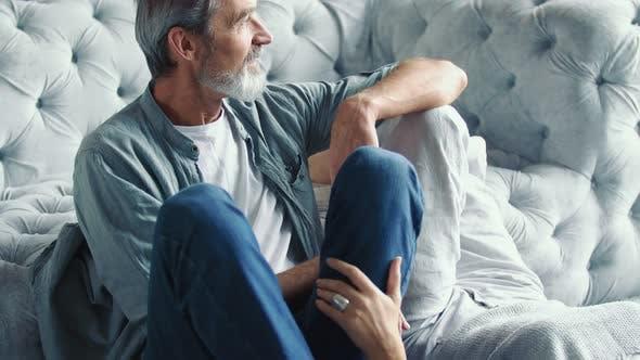Aged Couple Sitting Near the Sofa