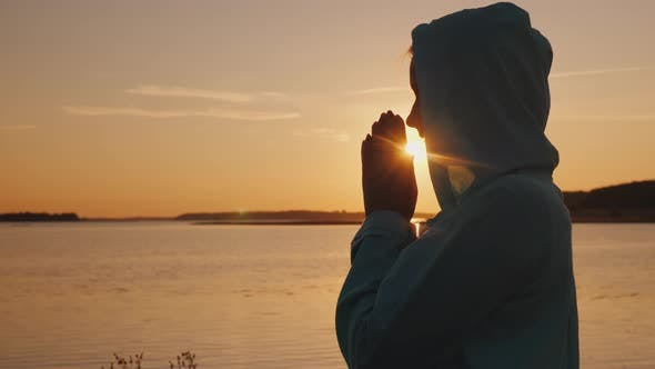 Thumbnail for Silhouette of a Woman Praying at Sunset By the Lake