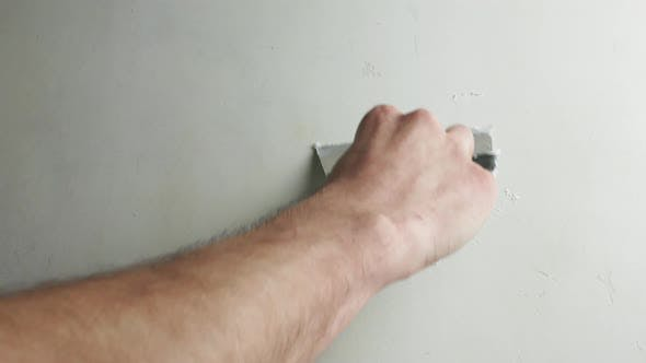 Thumbnail for Hand with a spatula smooths out the unevenness of the concrete wall.