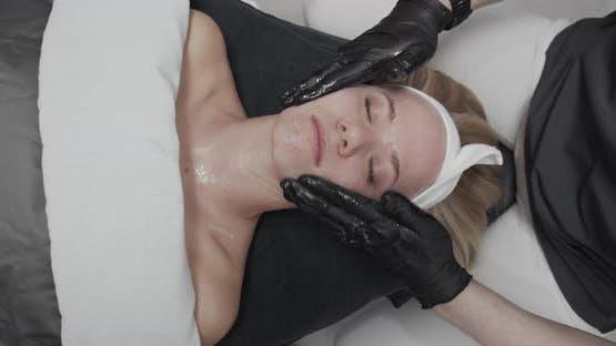 Woman Receiving Facial Massage In Beauty Salon