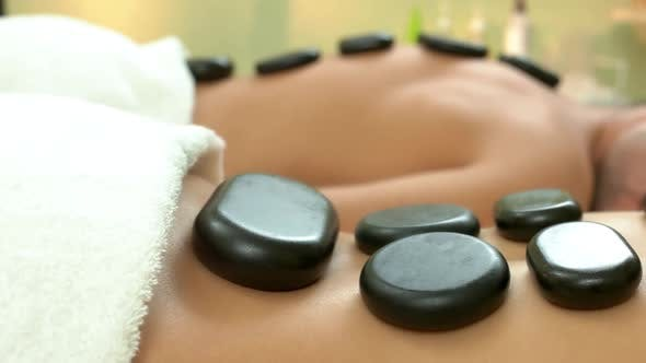 Close Up of Female Body with a Lot of Black Stones