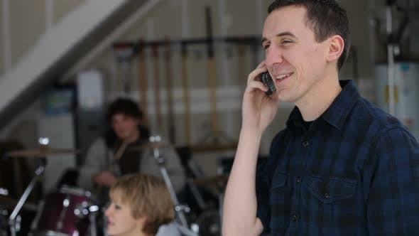 Young man in garage with band talking on cell phone