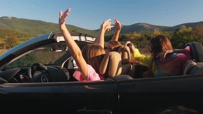Girlfriends in a Convertible Car Waving Hands