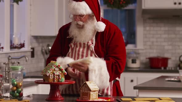 Thumbnail for Santa Claus in kitchen decorating gingerbread house