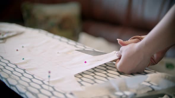 Thumbnail for Young Woman Seamstress Cutting the Cloth Following the Soap Marks