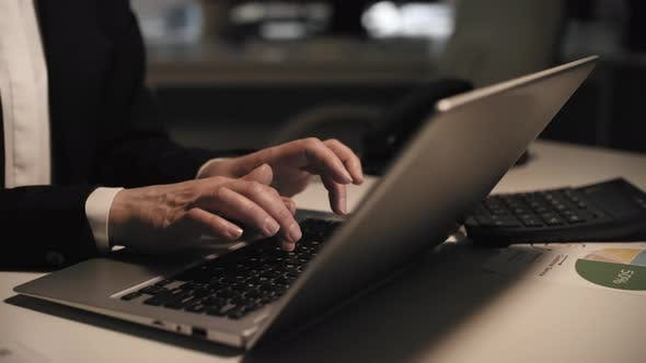 Thumbnail for Female Company Employee Typing on Laptop Late at Night in Office