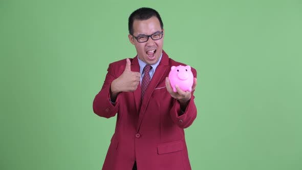 Thumbnail for Happy Asian Businessman with Eyeglasses Holding Piggy Bank and Giving Thumbs Up