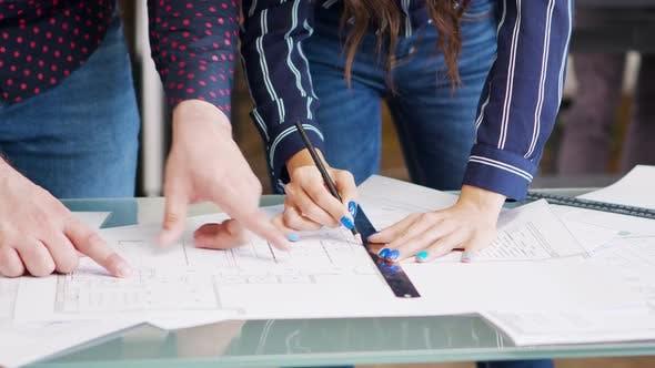 Close Up Hands of Female Designer Drawing on Blueprints