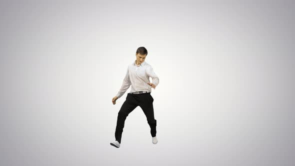 Young Man Dressed in White Shirt and Black Pants Jumping in the Frame and Starting To Dance Break