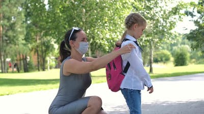 Mother Puts Safety Mask on Pupil Girl Near School
