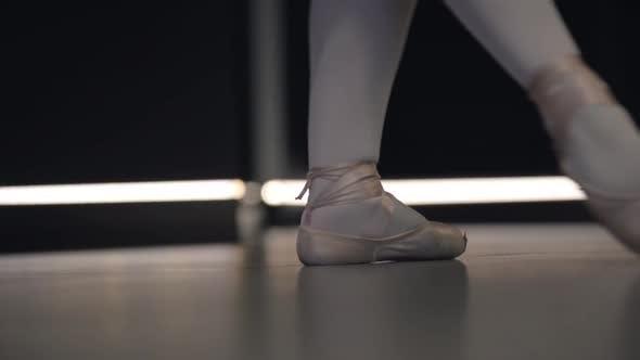 Thumbnail for Elegante Ballerina bewegt die Füße zusammen und steht auf Zehenspitzen. Nahaufnahme der Füße des Balletttänzers