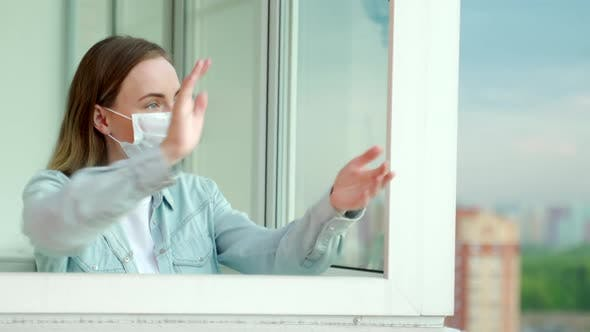 Thumbnail for Woman Applauds on the Balcony of Her Apartment, Thanking the Medical Services for Covid-19
