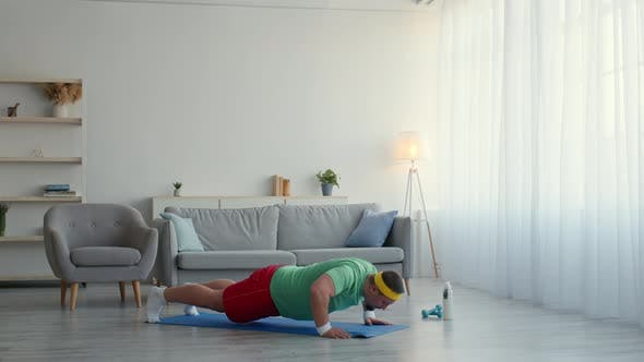 Chubby Guy in Sport Clothes Practicing Burpee Exercise at Home Doing Pushups and Jumping Slow Motion