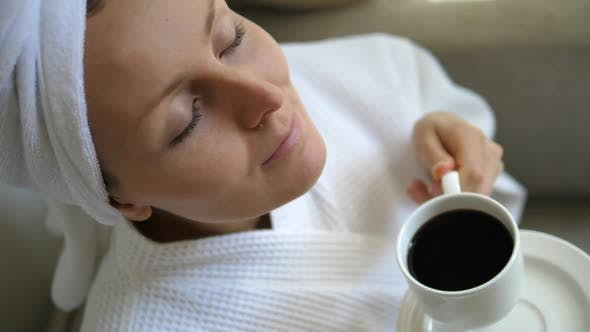 Thumbnail for Woman Smelling Coffee In Bathrobe After Morning Shower