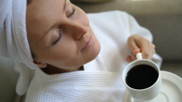 Thumbnail for Frau riechen Kaffee im Bademantel nach der morgendlichen Dusche