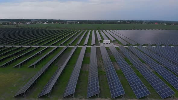 Aerial Drone View Into Large Solar Panels at a Solar Farm at Cloudy Summer Evening. Solar Cell Power