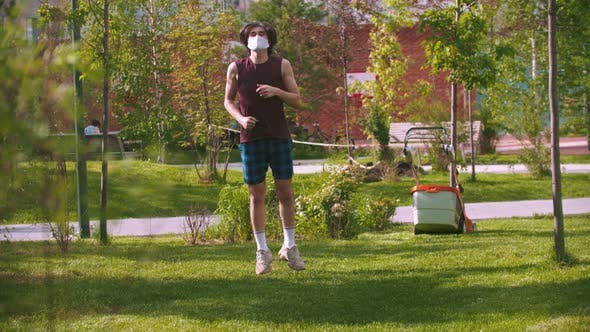 Cover Image for A Young Man in Medical Mask Warming Up in the Park Then Continue Running
