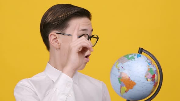Schoolboy Holding Earth Globe Pointing Finger Choosing Destination Yellow Background