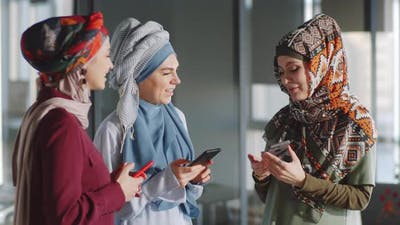 Muslim Female Colleagues Using Smartphones and Chatting