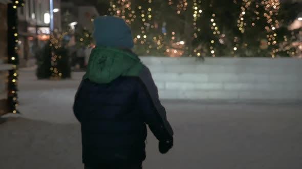 Kind läuft auf verschneiter Straße mit Weihnachtslichtern