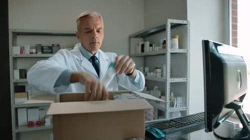 Pharmacist Unpacking Delivery From Stock Indoor of Drug Store Interior