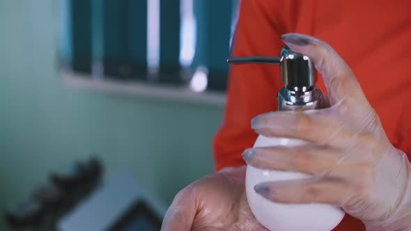 Doctor in Gloves Cleans Hands with Antiseptic Closeup