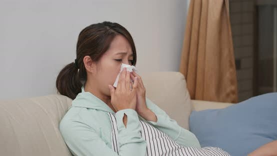 Cover Image for Sick woman sneeze and sit on sofa at home