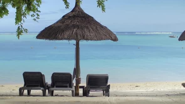 Thumbnail for View of Empty Chaise-longue Near Native Sun Umbrella Against Blue Water, Mauritius Island