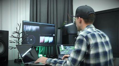 Freelancer video editor works at laptop computer.