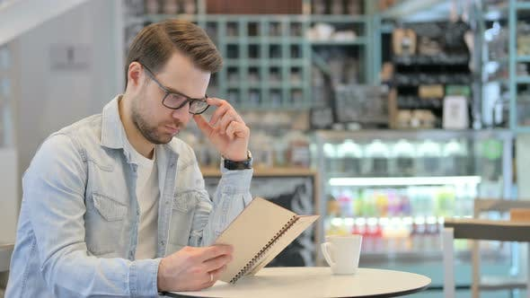 Thumbnail for Man Reading Book in Cafe