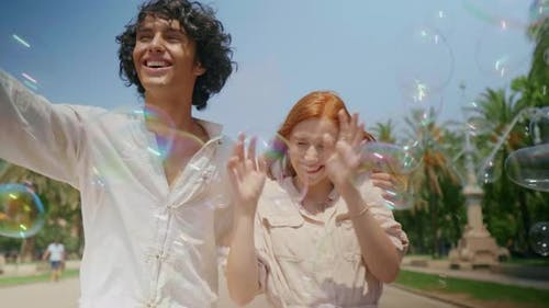 Portrait of Love Couple Catching Soap Bubbles, Romantic Man and Woman Having Fun