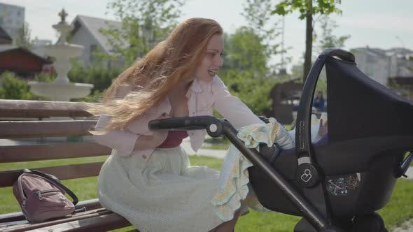 Thumbnail for Young Happy Redhead Mother Sitting on Bench Near the House with Baby Carriage and Smiling and