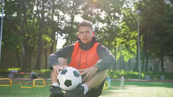 Thumbnail for Football Coach Sitting on the Artificial Turf of the Outdoors Sport Ground