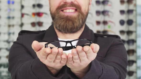 Thumbnail for Bearded Man Smiling Holding Out Glasses To the Camera