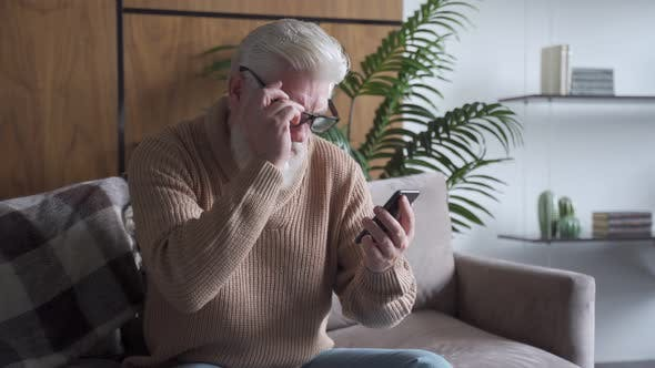 An Elderly Man with a Gray Beard Is Sitting on the Sofa Reading Bad News on a Smartphone