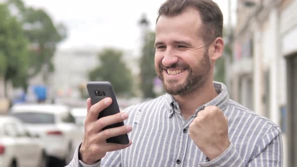 Thumbnail for Man Excited for Success on Smartphone